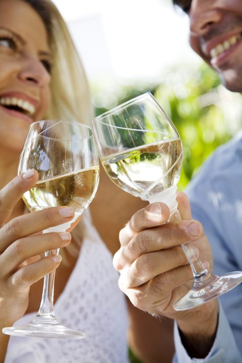 Couple toasting with glasses of white wine