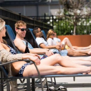 Residents at The Concord laying on lounge chairs by the swimming pool