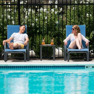 couple in lounge chairs by the concord apartments pool